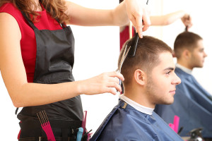 Beautiful girl hairdresser cut guy in beauty salon
