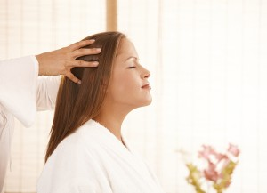 Portrait of young woman enjoying head massage with closed eyes,